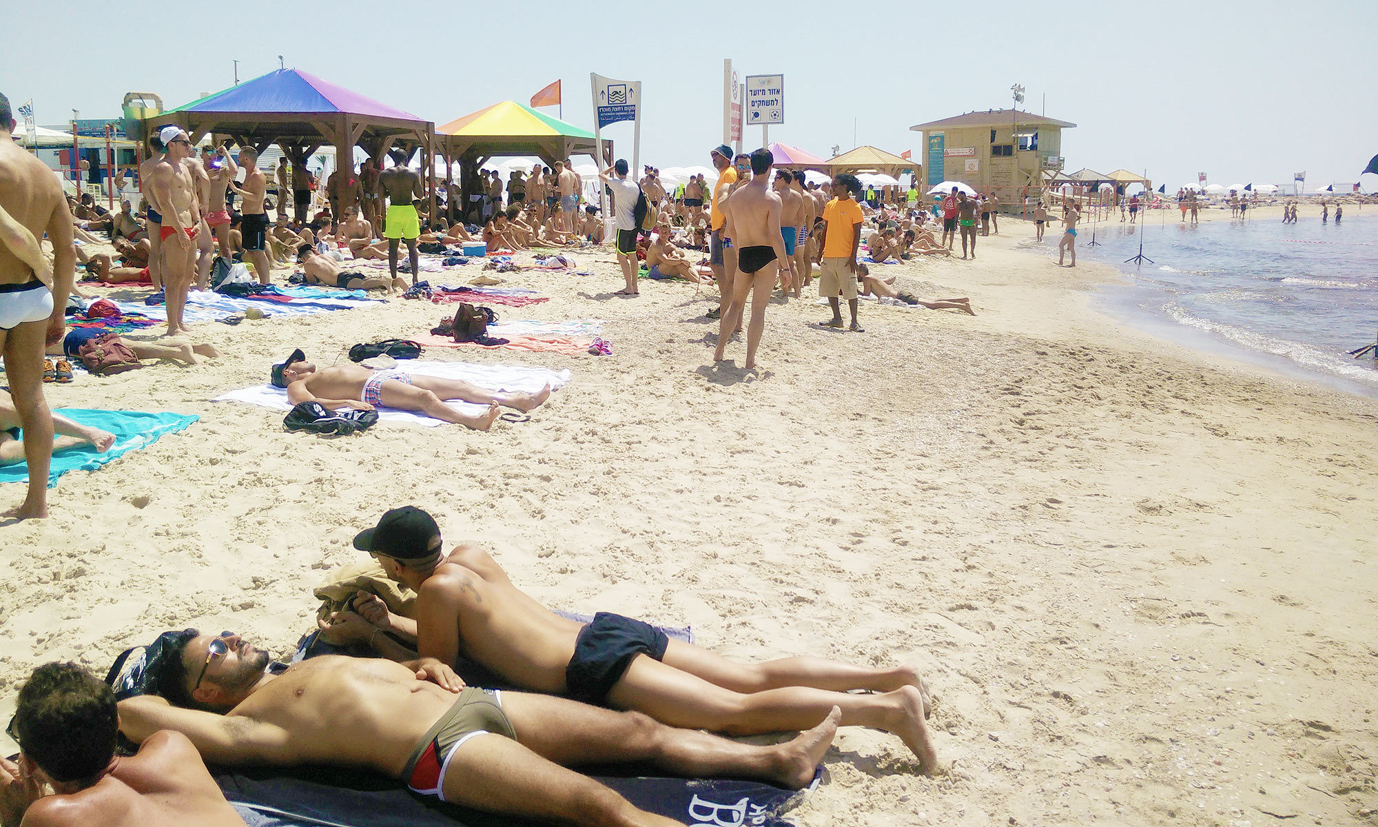 many men sunbathe or stroll around the gay beach called Hilton Beach in Tel Aviv