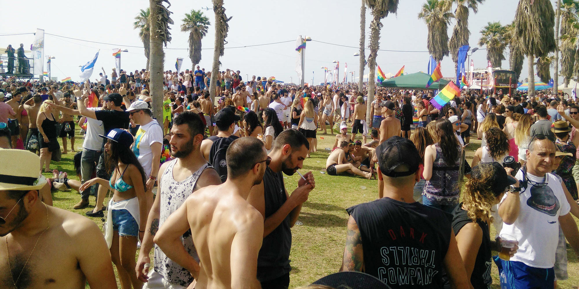 thousands celebrate Tel Aviv Pride at Charles Clore Park, some with bare chest because of the heat