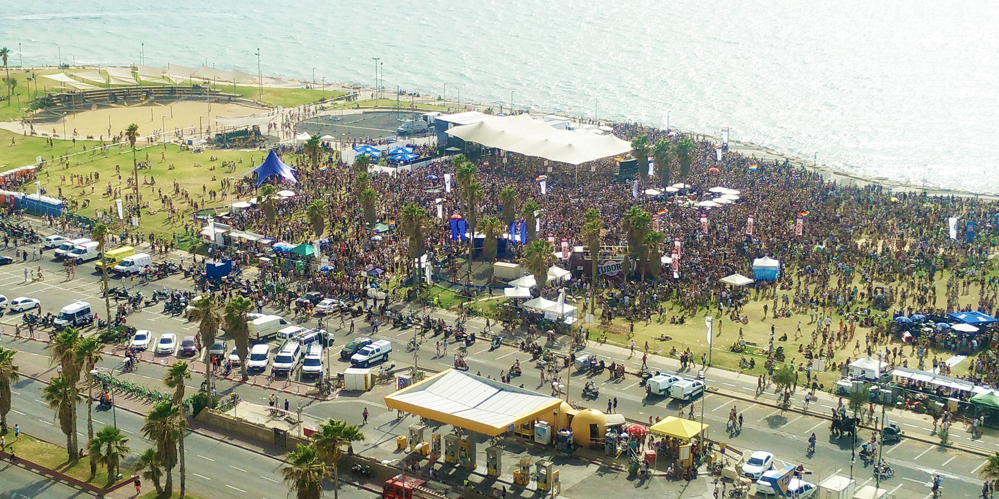 overview of the Charles Clore Park with roofed Pride stage and many thousands celebrating