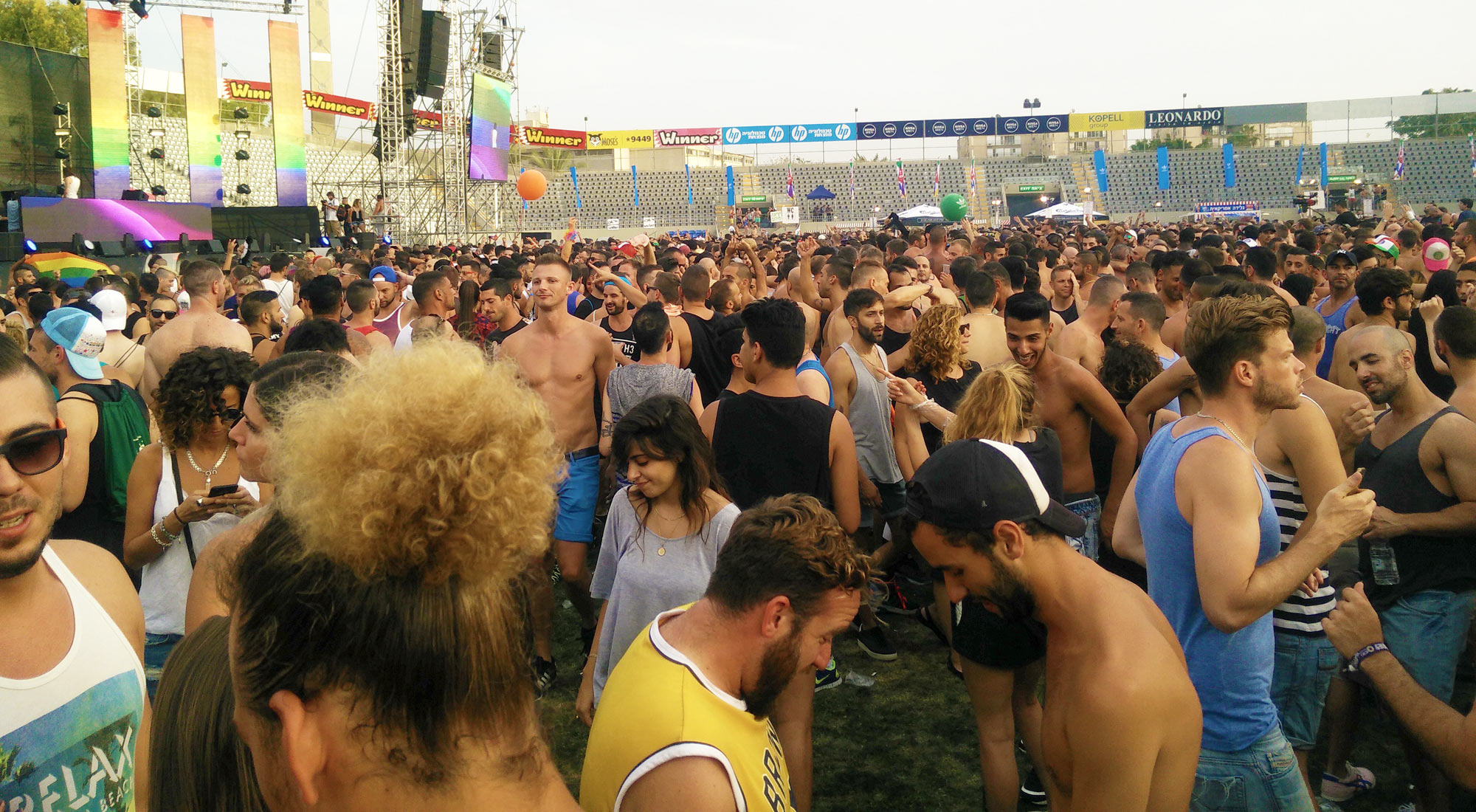 dancing people and stage show of the open-air disco with DJ Offer Nissim at Bloomfield Stadium for Tel Aviv Pride 2016