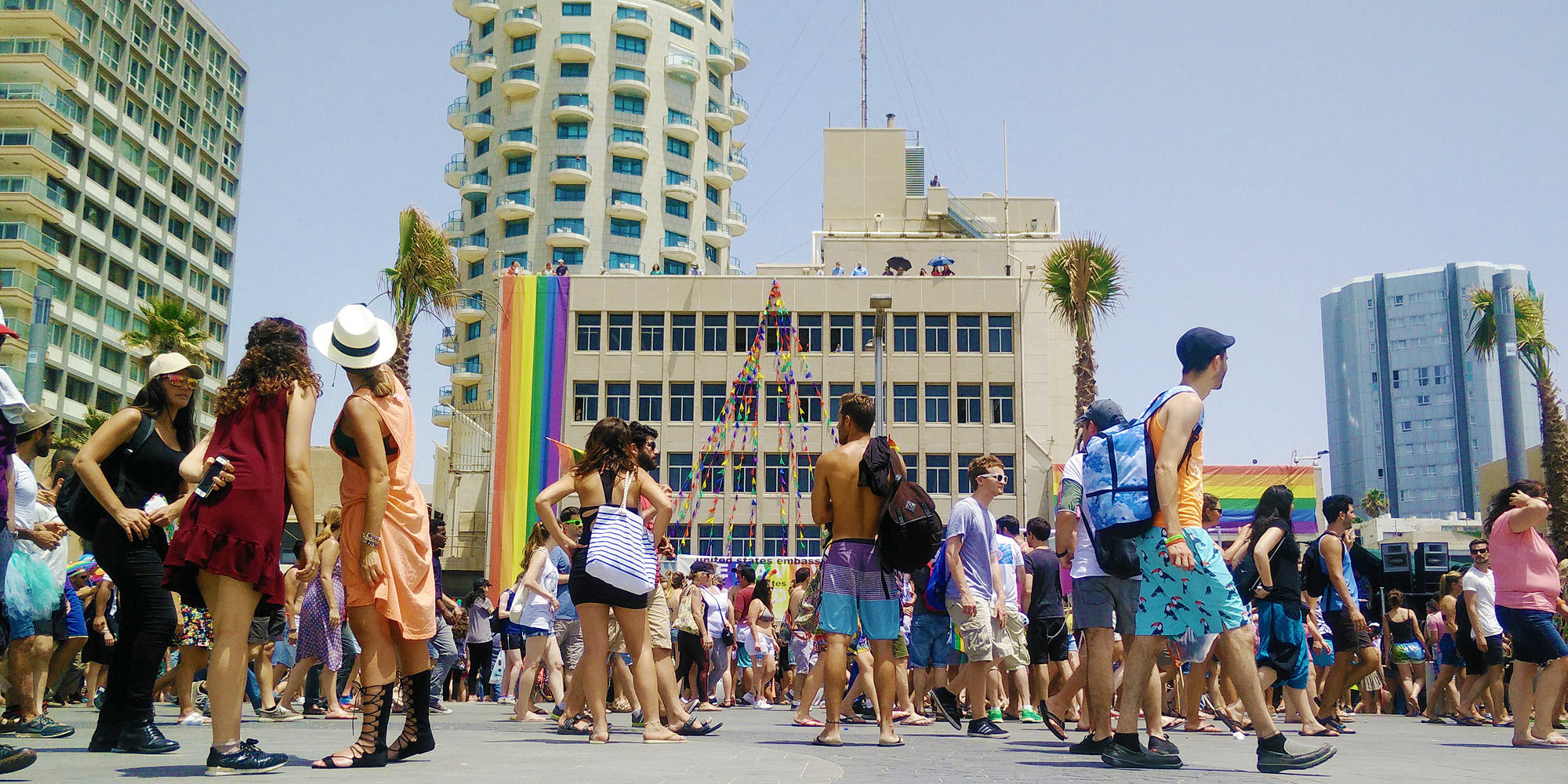 participants of the Tel Aviv Pride walk down the beach promenade in front of the US embassy with a long rainbow flag and the Hotel Isrotel